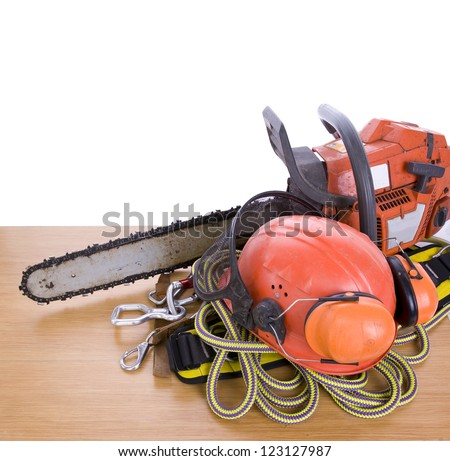 tree surgeon tools including chainsaw, helmet, harness, ear defenders and rope on desk