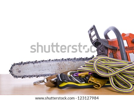 tree surgeon tools on desk including chainsaw, harness and rope