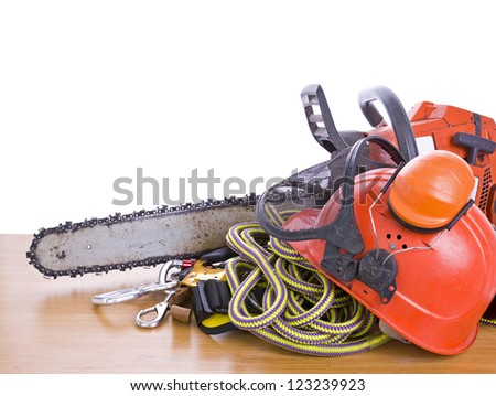 tree surgeon tools on desk including chainsaw, helmet, harness, ear defenders and rope