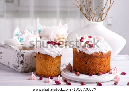Tree tasty decorate Easter cakes lie on a round white wooden plate on a   white wooden table.  A tray with cakes and flowers  stand on the table.