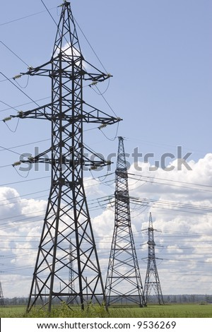 tree towers high voltage equipment in meadow