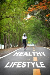 Tree tunnel with healthy lifestyle word and sportswoman ride bike on road, Business work life balance concept and stay active with relaxation idea