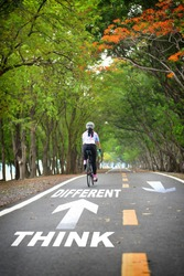 Tree tunnel with think different word and sportswoman ride bike on road, Business work life balance concept and stay active with relaxation idea