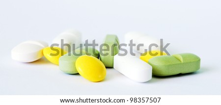 Tree yellow and green tablets and four white pills