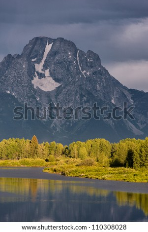 Treeline on the shore of the Snake River is selectively lit with Mount Moran in the background from the Oxbow Bend Overlook at Grand Teton National Park near Jackson, Wyoming