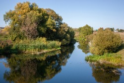 Trees and blue sky are reflected in the river. Don river at dawn in the Tula region of Russia. Thickets of reeds near the water in the morning sun.