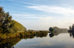 Trees and bushes around a Dutch lake with a mirror-smooth water surface. The photo was taken in autumn near the village of Lage Zwaluwe, North Brabant. Some haze is still visible in the background.