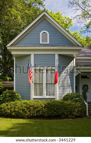 Trees and flags and victorian home with inviting lawn