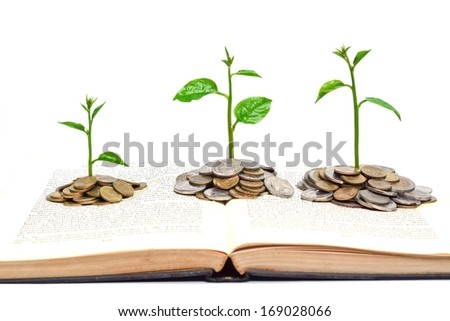 trees growing from books with coins / A big open book with coins and tree. \