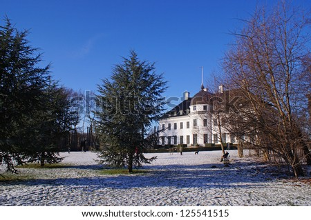Trees in front of Bernstorff Palace on a sunny winter day with snow on the ground