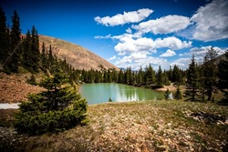 Trees reflect off a lake at the foot of Revenue Mountain in the Upper Geneva Creek near Grant, Colorado.