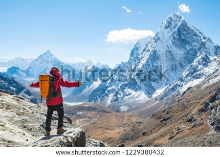 Trekker standing at the edge of the mountain cliff and looking to the beautiful view of Mt.Ama Dablam (6,812 m) and Cholatse  (6,440 m) view on the way to Cho La pass, Nepal.