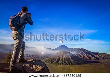 Trekker taking photo of Gunung Bromo volcano in Java, Indonesia