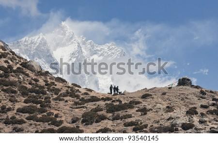 Trekkers in the Himalayas standing against peak Lhotse (8516 m) - Nepal