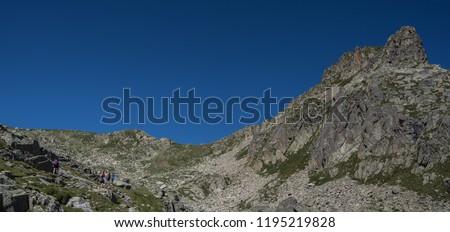 Trekkers on ascent to Port de Caldes de Colomers mountain pass at 2,572 m ASL, Aiguestortes & Estany de Sant Maurici National Park, Pyrenees, Spain #1195219828