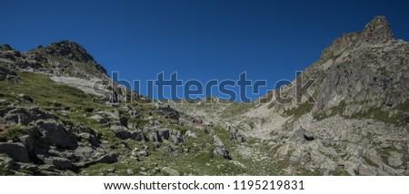 Trekkers on ascent to Port de Caldes de Colomers mountain pass at 2,572 m ASL, Aiguestortes & Estany de Sant Maurici National Park, Pyrenees, Spain #1195219831