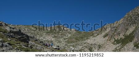 Trekkers on ascent to Port de Caldes de Colomers mountain pass at 2,572 m ASL, Aiguestortes & Estany de Sant Maurici National Park, Pyrenees, Spain #1195219852