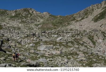 Trekkers on final ascent effort to Port de Caldes de Colomers mountain pass at 2,572 m ASL on trail GR11.18, Aiguestortes & Estany de Sant Maurici National Park, Pyrenees, Spain #1195215760