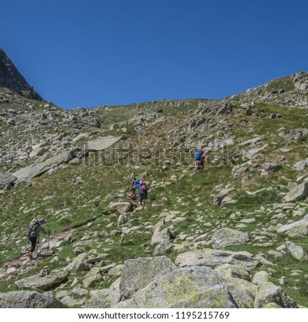 Trekkers on final ascent effort to Port de Caldes de Colomers mountain pass at 2,572 m ASL on trail GR11.18, Aiguestortes & Estany de Sant Maurici National Park, Pyrenees, Spain #1195215769