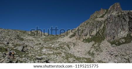 Trekkers on final ascent effort to Port de Caldes de Colomers mountain pass at 2,572 m ASL on trail GR11.18, Aiguestortes & Estany de Sant Maurici National Park, Pyrenees, Spain #1195215775