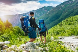Trekking in mountains. Mountain hiking. Tourists with backpacks hike on rocky way near river. Wild nature with beautiful views. Sport tourism in Svaneti, Georgia. Hikers and climbers in mounts