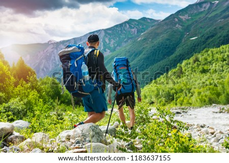 Trekking in mountains. Mountain hiking. Tourists with backpacks hike on rocky way near river. Wild nature with beautiful views. Sport tourism in Svaneti, Georgia. Hikers and climbers in mounts #1183637155