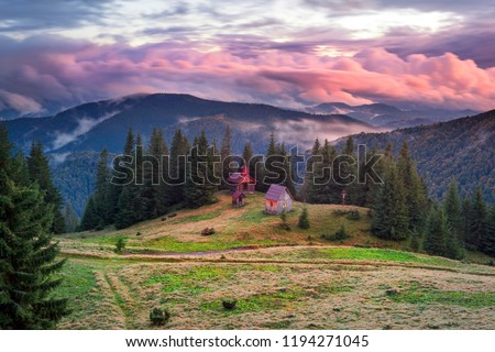 Trekking in the fall in a severe cold to a high-altitude wooden church on the roving of Rogneska Christian in the misty September. Coniferous and deciduous forests in fogs panorama #1194271045