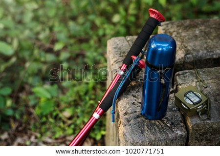 Trekking pole, water bottle and compass isolated on a rock outdoor #1020771751