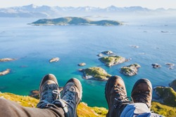 trekking shoes on feet of couple of travelers hikers sitting on top of the mountain in Norway with the beautiful view, trekkers selfy with norwegian landscape