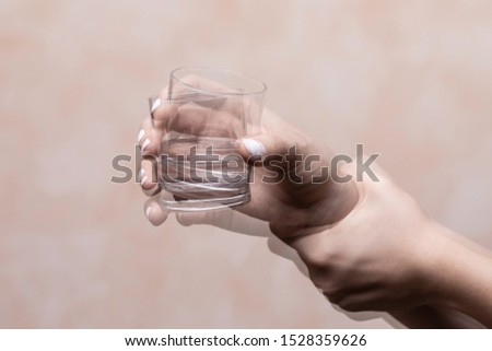 Trembling hand holding glass with alcohol drink Stock photo ©
