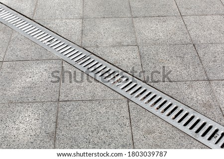 Photo of  Trench drain gray with steel purification grate on granite stone tile road improvement of the city, close up details drainage system, nobody.