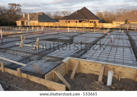 Trenches and rebar prep work for a house foundation.