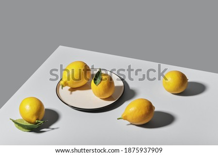 Trending colors of 2021. Yellow illuminating lemons on Ultimate gray tablecloth. Isometric view minimal still life.
