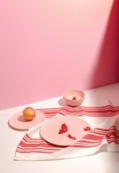 Trending colors. Plates with fruits and berries on tablecloth with red and white grid on pink background. Isometric view minimal still life. Minimal summer composition. Long harsh shadows. Copy Space