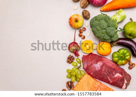 Trending paleo/pegan diet. Healthy balanced food concept. Set of fresh products, raw meat, salmon, vegetables and fruits. Stone concrete background, copy space, top view #1557783584
