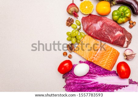 Trending paleo/pegan diet. Healthy balanced food concept. Set of fresh products, raw meat, salmon, vegetables and fruits. Stone concrete background, copy space, top view #1557783593