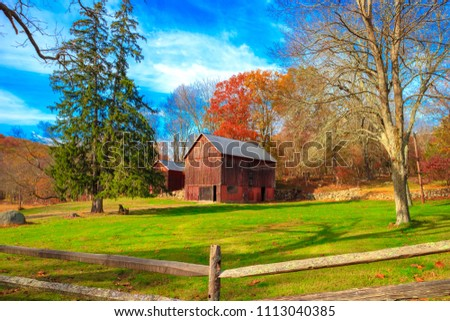 Trendition red wooden barn surround by blue sky, green grass and autumn trees. Vintage style photo was taken on the mountain in Fall season in New York, USA.