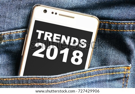 Trends 2018 inscription on phone screen / Smartphone in front jeans pocket with trends 2018 inscription  #727429906