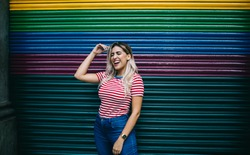 Trendy adolescent teenager dressed in casual apparel smiling and laughing at colorful promotional background, happy Hispanic hipster girl 20 years old rejoicing near copy space publicity area in city