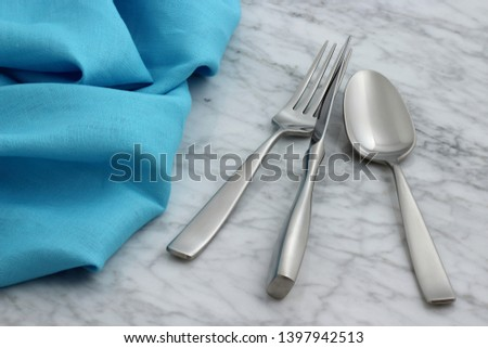 trendy and beautiful silverware set styled on linen double hemstitch napkin and antique carrara marble #1397942513