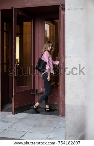 Trendy and fashionable beautiful young woman in casual business outfit goes through spinning doors into office building or office, looks into camera confident and serious, about to start work day