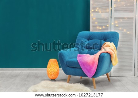 Trendy armchair with folding screen near shaded spruce wall