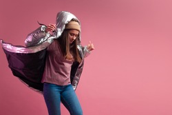 Trendy autumn and winter clothing, Studio shot on a pink background, copy space. A cool woman in a shiny silver down jacket and a knitted hat