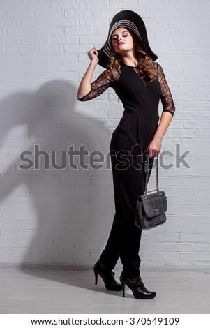 trendy beautiful girl in elegant black dress and hat #370549109