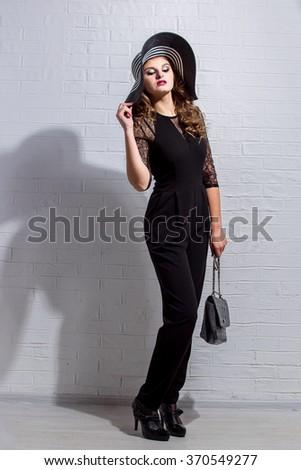trendy beautiful girl in elegant black dress and hat #370549277