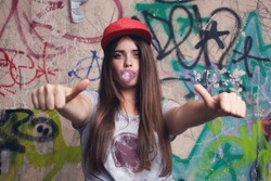 trendy beautiful long haired model posing on graffiti background. Blow bubblegum and show thumb up. red cap. grey t-shirt.