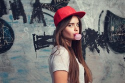 trendy beautiful long haired young model posing on graffiti background. Blow bubblegum. red cap. grey t-shirt.