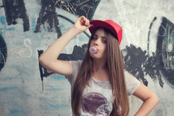trendy beautiful long haired young model posing on graffiti background. Blowing bubblegum. red cap. grey t-shirt.