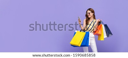 Trendy beautiful young Asian woman carrying colorful bags shopping online with mobile phone isolated on purple banner background with copy space