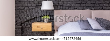 Trendy bedroom interior in modern home with gray pillows on bed, pastel pink headboard, pendant lamp, brick wall and plant standing on wooden side table #712972456
